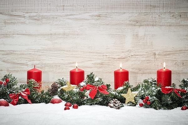 Vier rote Kerzen, drei davon brennen, stehen auf Tannenzweigen, die festlich geschmückt sind.