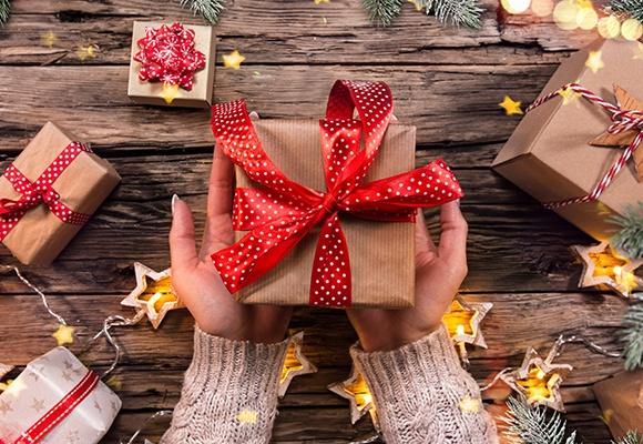 Frauenhände halten ein in braunem Papier eingewickeltes Geschenk mit rot-weißer Schleife. Im Hintergrund sind weitere Geschenke und sternenförmige Kerzen.