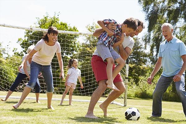 Familie mit drei Generationen spielt Fußball auf grünem Rasen. Der Vater trägt seinen Sohn zum Ball.