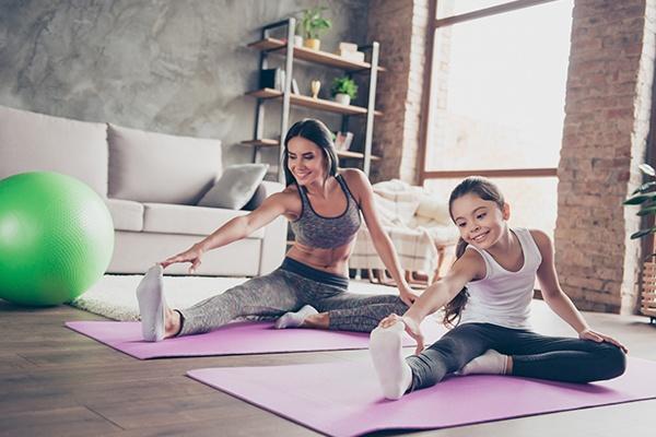 Eine Frau und ein Mädchen machen Streckübungen auf einer rosa Yogamatte im Wohnzimmer.