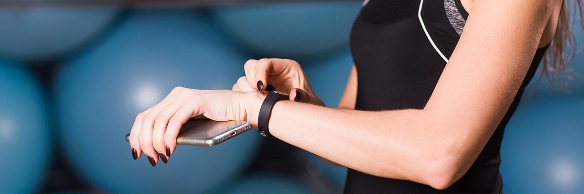 Eine Frau im schwarzen Top hält in der einen Hand ein silbernes Smartphone und stellt mit der anderen Hand ein Fitnessarmband ein. Der Hintergrund ist blau.