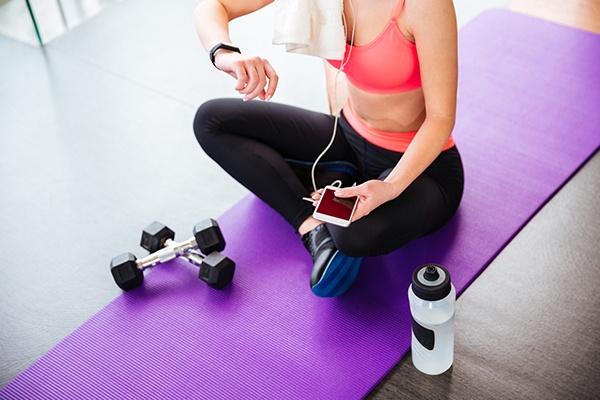 Eine bauchfreie Frau sitzt auf einer lila Yogamatte neben Hanteln und Wasserflasche, dabei prüft sie ihr Fitnessarmband.