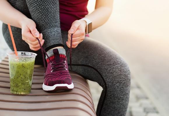 Frau bindet ihren lila-pinken Sportschuh im Sitzen zu, während ein grüner Smoothie vor ihr auf der Bank steht.
