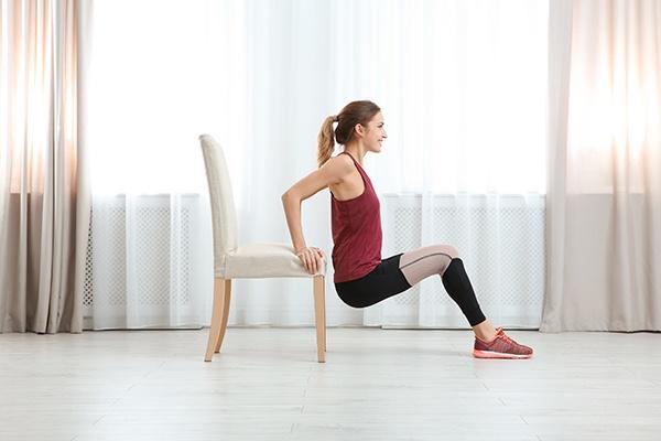Frau mit rotem Top macht Dips mit dem Sessel, indem die Arme sich auf der Sitzfläche abstützen und das Gesäß frei schwebt.