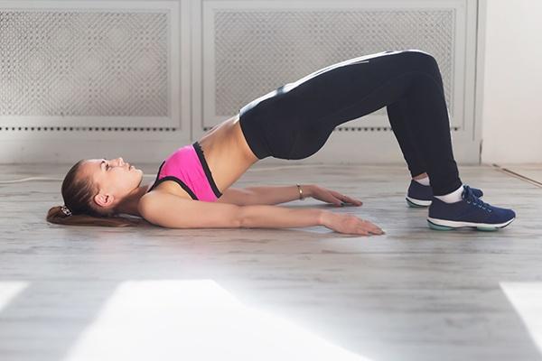 Bauchfreie Frau trainiert die Kraftbrücke, indem die Arme am Boden liegen und das Gesäß schwebt.