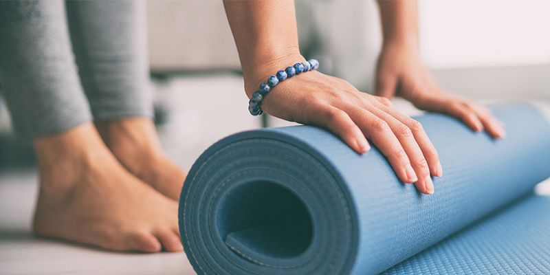 Frau rollt barfuß mit blauem Kugelarmband eine blaue Yogamatte auf oder zusammen.