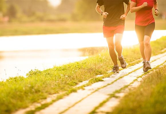 Ein Mann und eine Frau joggen auf einem schmalen Pfad neben einem See im Grünen. Die Sonne geht unter und spiegelt sich im Wasser.