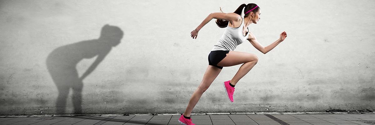 Eine Frau sprintet mit pinken Sportschuhen nach links, während ihr Schatten keuchend zurückbleibt.