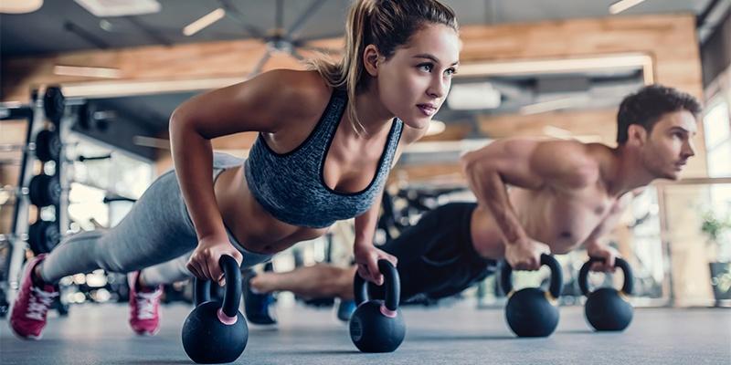 Ein Mann und eine Frau sind im Fitnessstudio und drücken sich von Hanteln mit Griffen nach oben in den Liegestütz auf Zehenspitzen.