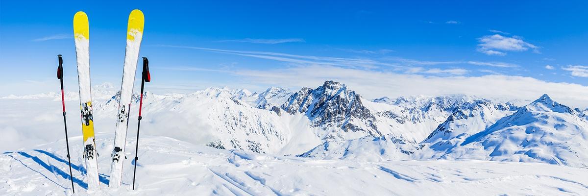 Zwei Skier und Skistöcke stecken im Schnee, während eine Gondel im Hintergrund hochfährt. Der Blick geht über ein Gebirge.