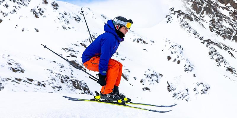 Ein Mann in blauer Jacke und oranger Skihose springt mit seinen gelben Skiern einen Hang herunter.