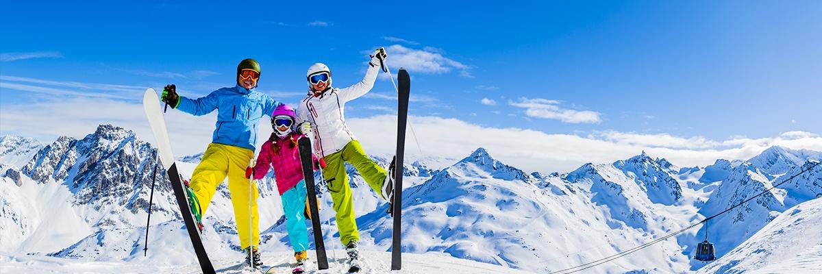 Eine dreiköpfige Familie in bunter Skiausrüstung hebt gemeinsam jeweils ein Bein mit Skiern dran und lacht in die Kamera.