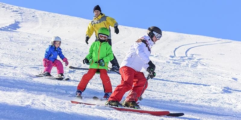 Eine vierköpfige Familie fährt in bunter Skiausrüstung langsam einen relativ flachen Hang herunter.