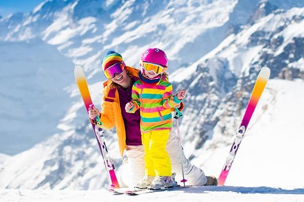 Mutter und Kind in sehr bunter Skiausrüstung stehen vor einem schneebedeckten Berg und lächeln in die Kamera.
