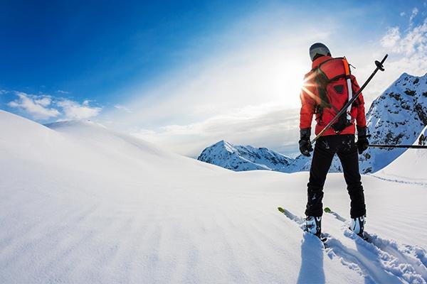 Ein Skifahrer mit roter Jacke versinkt mit seinen Skiern in unberüherten tiefen Schnee und zieht die ersten Linien.