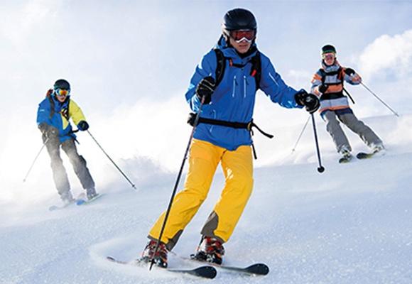Drei Skifahrer mit Skibrille und Skihelm fahren einen schneebedeckten Hang herunter.