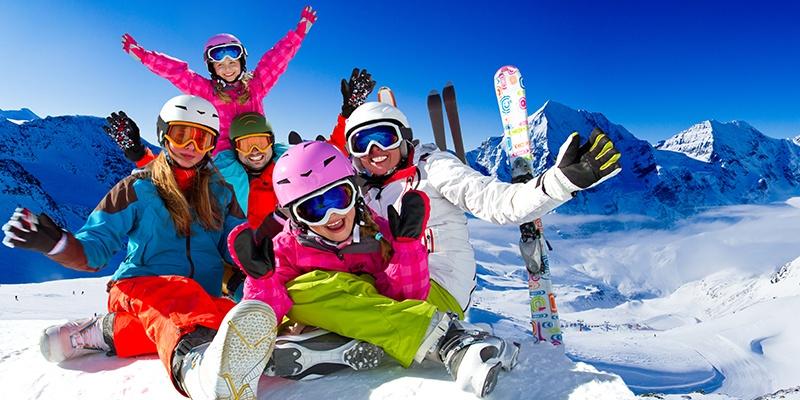 Eine Familie in knallig buntem Outfit steht auf einem verschneiten Berg. Im Hintergrund sieht man Skier und ein weites Gebirge.