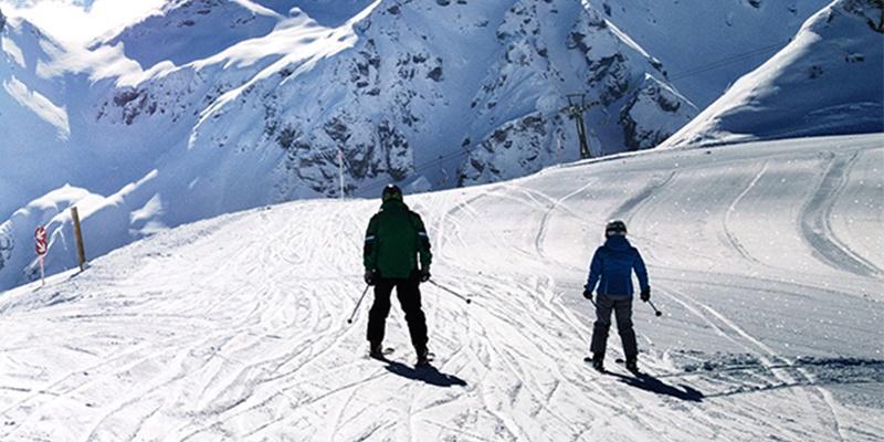 Zwei Skifahrer gleiten einen schwachen Hang bergab, im Hintergrund ist schneebedecktes Gebirge.