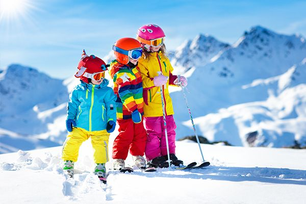 Drei kleine Kinder in sehr bunter Skiausrüstung schauen nach rechts. Im Hintergrund ist ein Gebirge.
