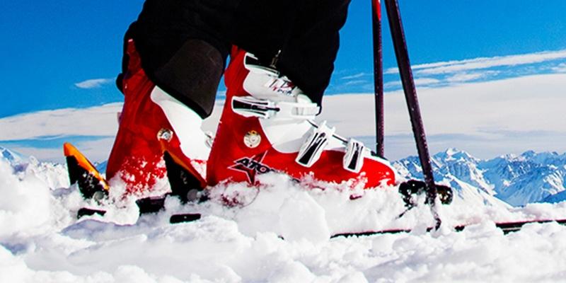 Im Hintergrund ist ein Gebirge, das in blau leuchtet, während vorn zwei rote Skischuhe über Schnee fahren.