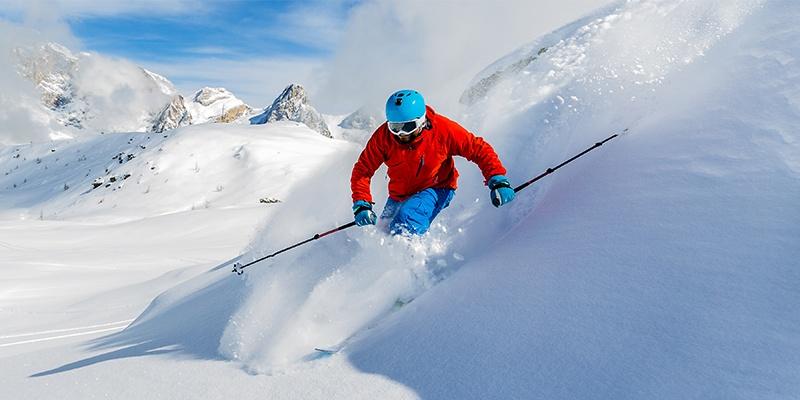 Ein Skifahrer im rot-blauen Outfit fährt sehr schnell über einen steilen Hang. Ringsherum ist Gebirge.