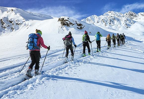 Eine Reihe mehrere Skifahrer folgt einer vorgegeben Spur im Schnee inmitten eines Gebirges.