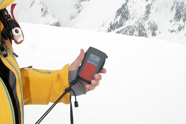 Ein Mann mit gelber Jacke hält ein Lawinensuchgerät. Um ihn herum liegt viel Schnee.