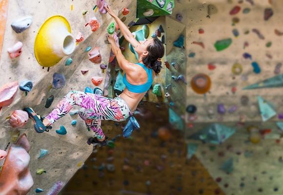 Muskulöse Frau klettert an einer bunten Kletterwand nach oben. Sie trägt eine bunte Hose und ein blaues Top.
