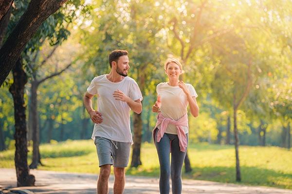 Ein Mann und eine Frau joggen durch einen Park mit grünen Bäumen.