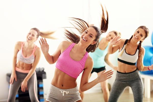 Vier Frauen tanzen glücklich dieselbe Bewegung und sind bauchfrei.