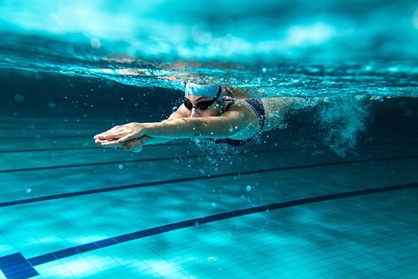 Eine Schwimmerin zieht unter Wasser mit Schwimmbrille und Haube Bahnen im blau schimmernden Schwimmbecken.