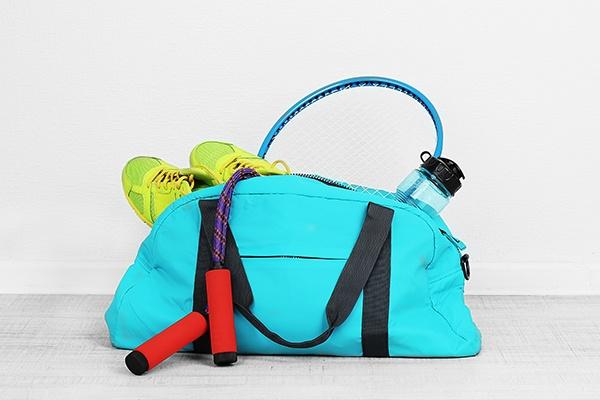 Eine türkise Sporttasche, gefüllt mit einem roten Springseil, grünen Laufschuhen und einer Wasserflasche steht auf einem weißen Untergrund.