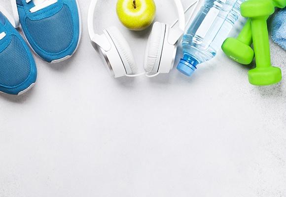 Verschiedene Sportmaterialien wie Joggingschuhe, grüne Hanteln, eine Wasserflasche, Köpfhörer und ein Handtuch liegen auf einem weißen Untergrund.