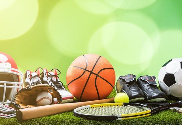 Verschiedene Sportausrüstungen wie Baseballschläger, Federballschläger, Boxhandschuhe, Fußballschuhe, Fahrradhelm und Co liegen auf Kunstrasen.