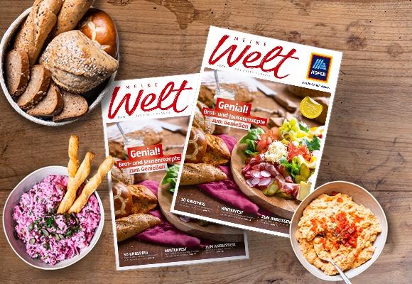 Zwei Exemplare des Meine-Welt-Magazins sind auf einem Holztisch aufgelegt. Daneben stehen eine Schüssel mit Brot und zwei Schüsseln mit Dips.