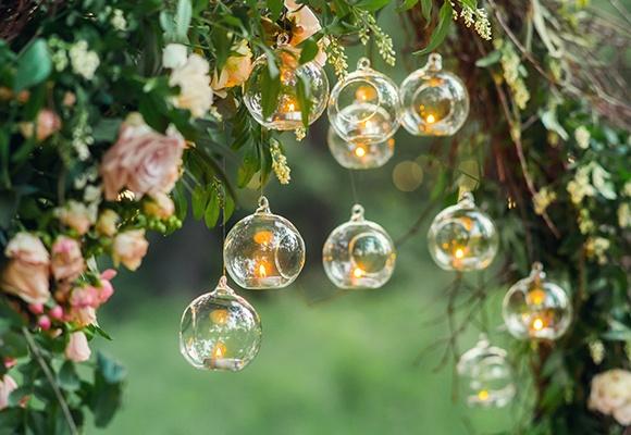 Brennende Teelichter hängen in einer Glaskugel unter einem Torbogen aus hellen Rosen.