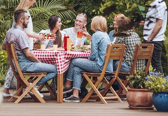 Eine Gruppe Freunde sitzt gemeinsam an einem Gartentisch auf Holzstühlen. Die Tischdecke ist rot-weiß kariert.