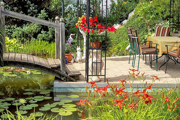 Gartenstühle und ein Tisch stehen auf einer Garteninsel, die über eine kleine Bogenbrücke über Wasser erreichbar ist.