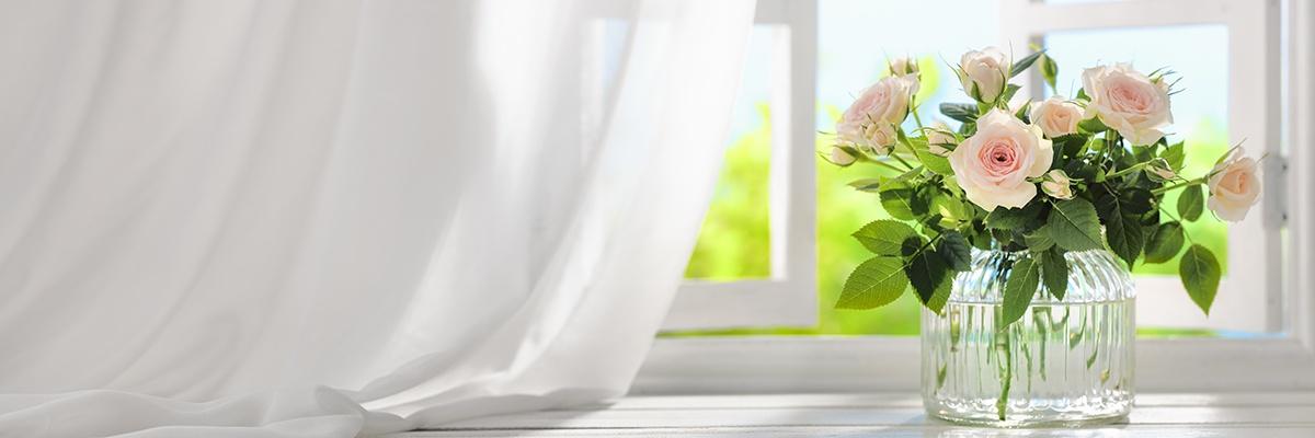 Hellrosa Rosen stecken mit Blättern in einer transparenten Vase. Im Hintergrund weht durch ein offenes Fenster ein weißer Vorhang.