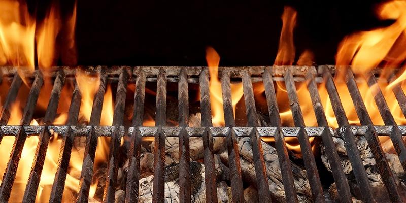 Ein Grillgitter unter dem brennende Kohlen zu sehen sind. Die Flammen reichen über das Grillgitter hinaus.