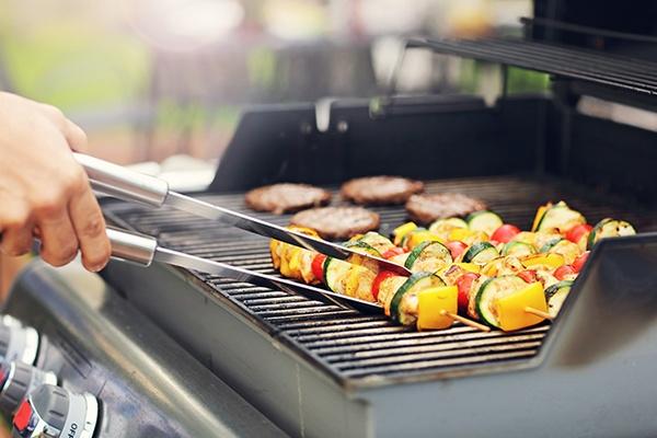 Auf einem Gasgrill liegen vier Burger Patties und mehrere Gemüsespieße. Man sieht eine Hand mit einer Grillzange die einen Gemüsespieß wendet.