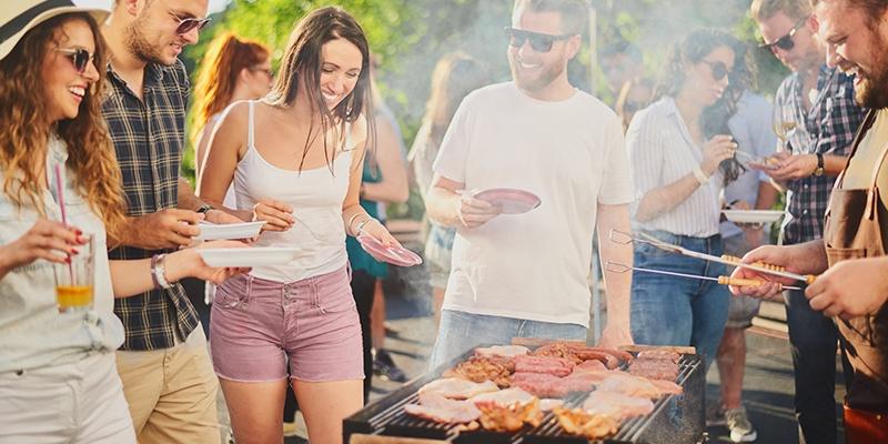 Mehrere Menschen stehen um einen Grill. In der Mitte steht der mit Fleisch belegte Grill. Rechts steht ein Mann mit Grillzange und Fleischgabel in der Hand.