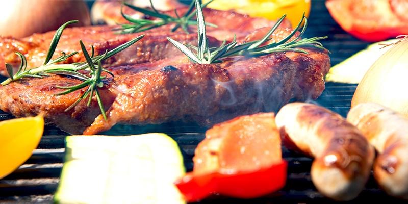 In Nahaufnahme werden Bratwürste, Steaks, Paprika, Zucchini und Zwiebel auf einem Rost gegrillt.