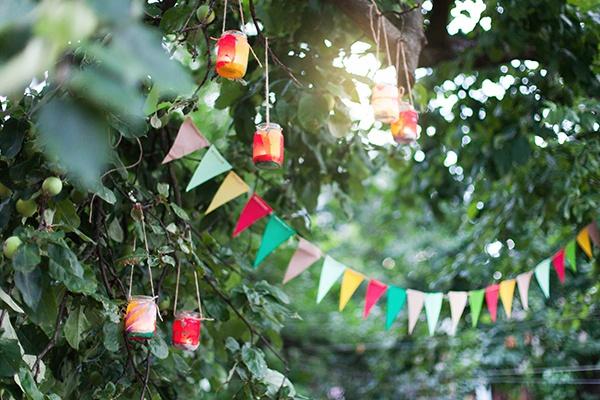 Zwischen Bäumen sind Girlanden mit dreieckigen Fähnchen und Windlichter gespannt.