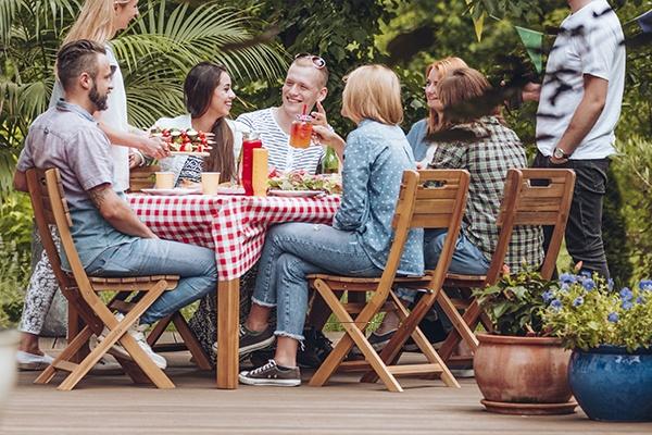Freunde sitzen gemeinsam an einem Gartentisch auf Holzstühlen, sie trinken und essen.