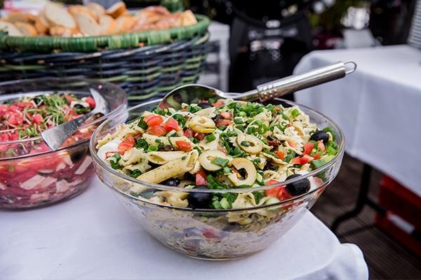 Zwei gut gefüllte Schüsseln mit Salat stehen auf einem Tisch. Vorn steht Nudelsalat und hinten Tomatensalat