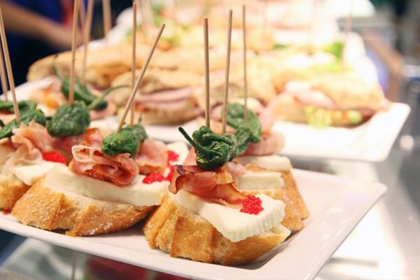 Auf Baguettescheiben ist Käse, Wurst und Gemüse aufgespießt, serviert auf viereckigen Tellern.