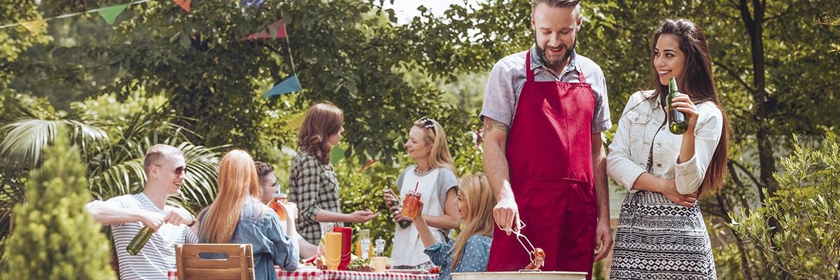 Freunde grillen gemeinsam im großen Garten. Der Grillmeister trägt eine rote Grillschürze und unterhält sich mit einer Frau, die ein Bier trinkt.