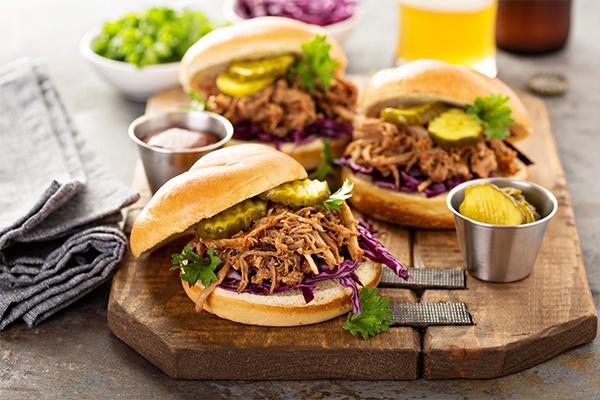 Drei selbstgemachte Burger liegen auf einem Holzbrettchen. Sie sind mit Petersilie, Rotkraut, Gewürzgurken und in Streifen geschnittenes Fleisch.