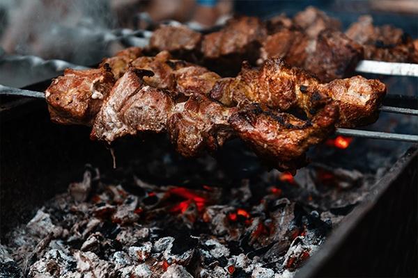 Aufgereihtes Fleisch auf einem Metallspieß wird über glühender Kohle gegrillt. Genannt: Churrasco aus Brasilien.